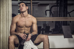Muscular young man resting in gym during workout Stock Photos