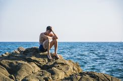 Muscular young man on rock by sea Stock Photo