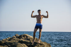 Muscular young man on rock by sea Royalty Free Stock Photos