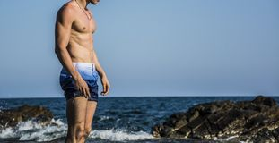 Muscular young man by sea shirtless against the Royalty Free Stock Photos