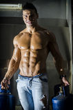 Muscular young man shirtless, carrying gas tanks Royalty Free Stock Images