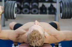 Muscular young man shirtless, training pecs on gym bench Stock Photography
