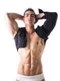 Muscular young man with single-sleeved shirt on naked torso Royalty Free Stock Photo
