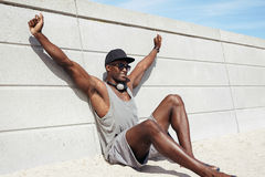 Muscular young man sitting on beach looking happy. Muscular young man sitting by a wall stretching his hands smiling. African male model on beach Royalty Free Stock Image