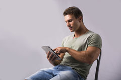 Muscular young man sitting on chair reading from ebook device. Pointing finger at screen Stock Photo