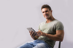 Muscular young man sitting on chair reading from ebook device Stock Photo