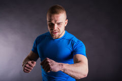 Muscular young man in sports outfit arms punching, smiling on dark background Stock Image