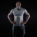 Muscular young man in sportswear on black background Royalty Free Stock Image