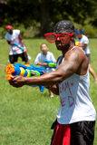 Muscular Young Man Squirts People With Water Gun Royalty Free Stock Images