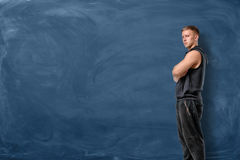 Muscular young man is standing his arms crossed and looking forward on blue chalkboard background Stock Photo