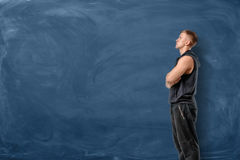 Muscular young man is standing his arms crossed and looking up on blue chalkboard background. Sport and healthy lifestyle. Keep fit. Athletic body Royalty Free Stock Photo