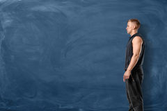 Muscular young man is standing and looking forward on blue chalkboard background. Sport and healthy lifestyle. Keep fit. Athletic body stock photography