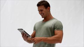 Muscular young man standing using tablet PC stock video