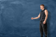 Muscular young man is stretching his fist before him and looking at it on the blue chalkboard background Stock Photo