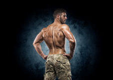Muscular young man in studio on dark background Royalty Free Stock Photography