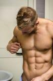 Muscular young man touching nipple piercing Stock Photo