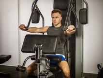 Muscular young man, training pecs on gym machine. Muscular young man, training pecs on gym cable machine stock photos