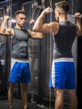 Muscular young man, training shoulders on gym machine. Muscular young man, training shoulders on gym cable machine royalty free stock photography