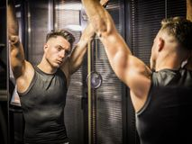 Muscular young man, training shoulders on gym machine. Muscular young man, training shoulders on gym cable machine stock photos