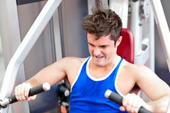 Muscular young man using a bench press Royalty Free Stock Photography
