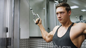 Muscular young man using a weights machine in the gym Stock Photo