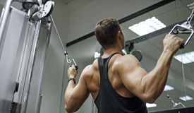 Muscular young man working out on a cable machine Royalty Free Stock Photo