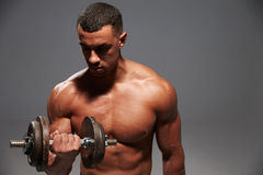Muscular young man working out with a heavy dumbbell Royalty Free Stock Photography