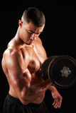Muscular young man working out with  heavy dumbbell Royalty Free Stock Image