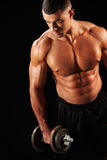Muscular young man working out with  heavy dumbbell Royalty Free Stock Images