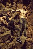 Muscular young men. Men bare-chested young pose twin brother models in jeans outdoor on mural background stock photos