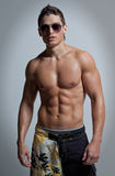 The muscular young naked sexy boy in sunglasses Stock Image