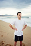 Muscular young runner resting after intensive morning jogging standing on the beach Stock Photos