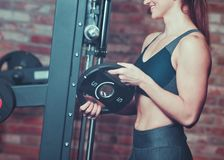 Muscular young smilling woman holds iron disk of barbell. Muscular young smilling woman holds iron disk of barbell stock photography