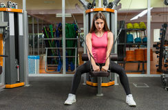 Muscular young sporty woman training on row machine royalty free stock photography