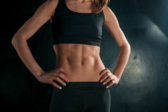Muscular young woman athlete on black Royalty Free Stock Image