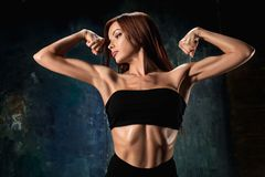Muscular young woman athlete on black. The view of muscular young woman athlete posing on black studio background Royalty Free Stock Photography