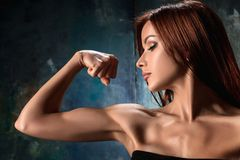 Muscular young woman athlete on black. The view of muscular young woman athlete posing on black studio background Stock Photography