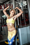 Muscular young woman athlete posing at gym with chain in hands Royalty Free Stock Photography