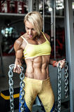 Muscular young woman athlete posing at gym with chain in hands Stock Photography
