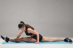 Muscular young woman athlete sitting in the split on gray Stock Photo