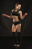 Muscular young woman athlete with a skipping rope Stock Images