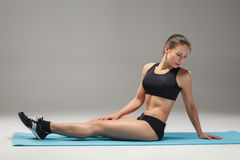 Muscular young woman athlete stretching on gray Stock Image