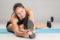 Muscular young woman athlete stretching on gray Royalty Free Stock Image