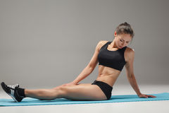 Muscular young woman athlete stretching on gray Royalty Free Stock Images