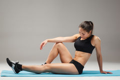 Muscular young woman athlete stretching on gray Royalty Free Stock Photography