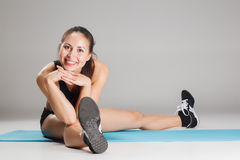 Muscular young woman athlete stretching on gray Stock Photos