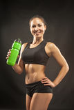 Muscular young woman athlete with a water on black Stock Image