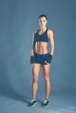 Muscular young woman posing in sportswear against black background Royalty Free Stock Photography