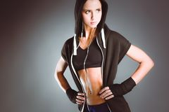 Muscular young woman posing in sportswear against black background Stock Photo
