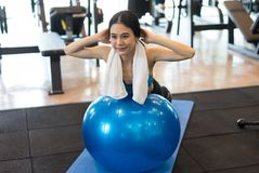 Muscular young woman smiling working out on the exercise fit bal. L at the gym,Fitness Concept,Lifestyle and people concept Royalty Free Stock Images